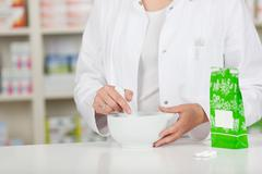 pharmacist crushing medicine in mortar at pharmacy counter - stock photo