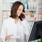 pharmacist using cordless phone while looking at computer - stock photo