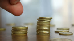 Two stacks of coins on the desk, fingers, loosing profits, close-up - stock footage
