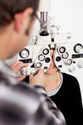 doctor and female patient in eye clinic - stock photo