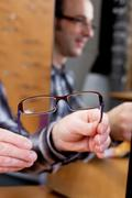 salesperson offering new glasses - stock photo