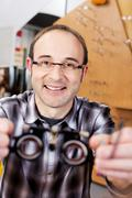 confident optician holding test lenses - stock photo