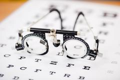 Eye test glasses on snellen chart Stock Photos