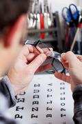 Optician fixing lens on frame at workshop Stock Photos
