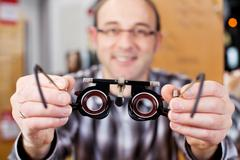Mature optician holding eye test glasses Stock Photos