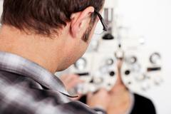 optician examining patient's eyes in examination room - stock photo