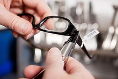 Optician's repairing glasses with pliers Stock Photos