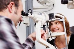 mature optician testing patient's eyes in examination room - stock photo