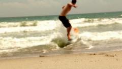 Stock Video Footage of Man Skim Boarding Surfing on the Beach