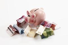 Piggy bank with euro notes and swiss francs on white background Stock Photos