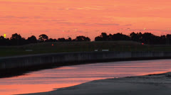 River Reflecting Pink Sunset next to airport 160GYAP 0018 NTSC Stock Footage