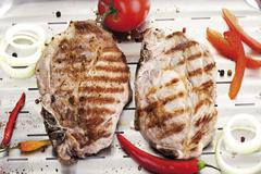 Grilled Pork chop on aluminium grill pan Stock Photos
