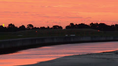 River Reflecting Pink Sunset next to airport 160GYAP 0018 PAL Stock Footage