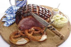 Roast Pork with Crackling, Pretzels and cabbage salad on wooden board, elevated - stock photo