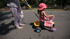 Mother rides daughter on trike Stock Footage