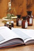 Homeopathic book, in background apothecary flasks Stock Photos