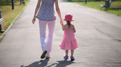mother and daughter dancing in park - stock footage