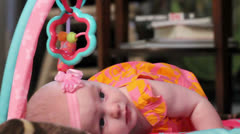 Baby girl on play mat figuring out movement Stock Footage