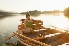 Nuori nainen istuu soutuvene järvi Kuvituskuvat