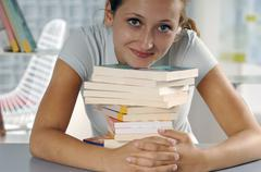 Stock Photo of Young woman holding pile of books