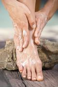 Stock Photo of Woman applying lotion to feet, low section