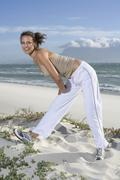 South Africa, Cape Town, Young woman exercising on beach - stock photo