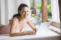 Stock Photo of Young woman in underwear using laptop