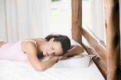 Nuori nainen nukkuu hotellihuoneen sängyssä Kuvituskuvat