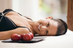 Young woman wearing neglige, relaxing on bed alongside tray with plums Stock Photos
