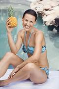 Young woman in bikini holding ananas - stock photo