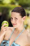 Stock Photo of Young woman in bikini holding apple, portrait, close-up