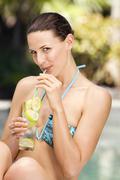Stock Photo of Young woman in bikini drinking with straw