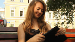 A young girl in a park with a tablet computer. summer - stock footage