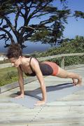 Young woman exercising yoga, doing a push-up - stock photo