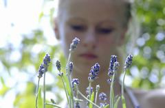 Young woman standing in lavender field, focus on lavender flowers at foreground, - stock photo