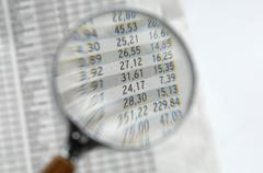 Stock quotations under magnifying glass, close-up - stock photo