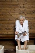 Germany, senior man having foot bath in health spa Stock Photos