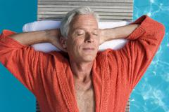 germany, senior man relaxing on float in pool, close-up, portrait - stock photo
