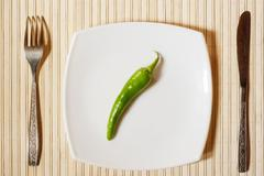 fresh green pepper on a white square plate. - stock photo