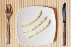 three pods of beans on a white square plate. - stock photo