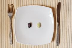 two pods to choose from on a white square plate. - stock photo