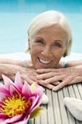 germany, senior woman leaning on edge of pool, portrait - stock photo