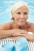 Stock Photo of germany, senior woman leaning on edge of pool, portrait