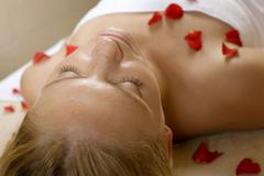 germany, woman lying on back, petals on chest - stock photo