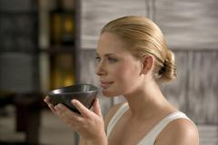 Stock Photo of germany, young woman holding tea bowl, close-up