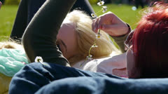 Happy Teen Friends Making Daisy Chains, Laying in Grass at a Park Stock Footage