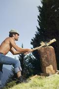 young man chopping wood, side view - stock photo