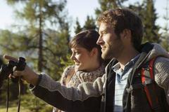young couple walking on mountains, man holding binocular - stock photo