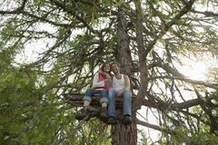 young couple sitting on tree house, embracing - stock photo