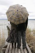 Stock Photo of Couple on jetty with umbrella, rear view